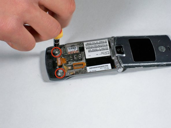 Unscrew the two screws holding the plastic speaker cover to the phone with a T5 screwdriver