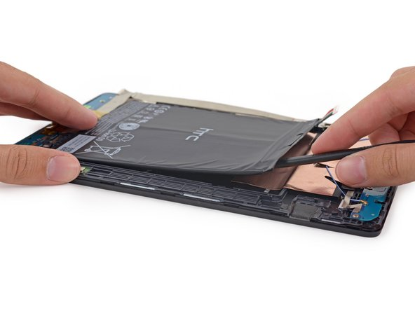 Alas, the battery is within our reach, but not our grasp: some fairly heavy-duty adhesive holds it fast in place.