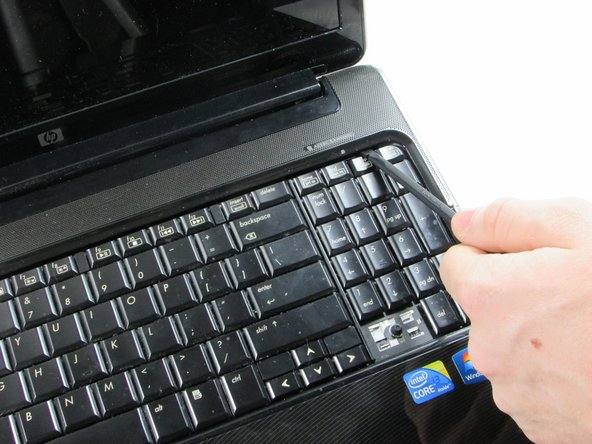 Use a plastic spudger to gently un-clip the top panel above keyboard.
