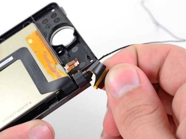 Gently roll the upper LCD ribbon cable and camera ribbon cable together and insert them  into the hinge opening.