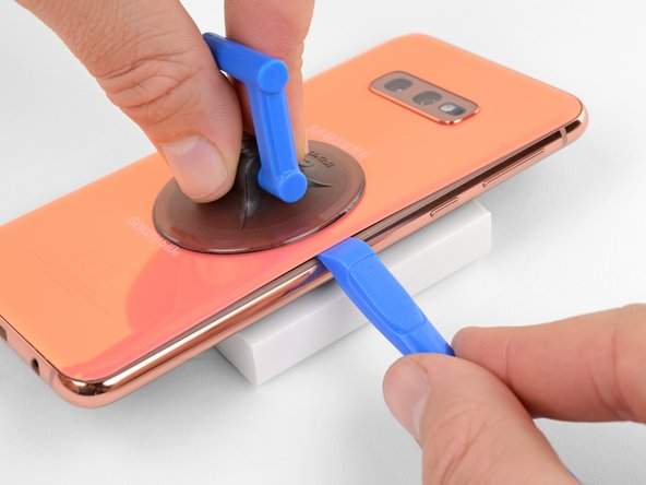 Slide the opening tool along the right edge of the phone to slice through the adhesive securing the back cover.