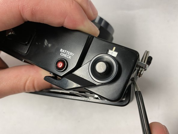 Push out the pin holding the back cover to the body of the camera using angled tweezers.