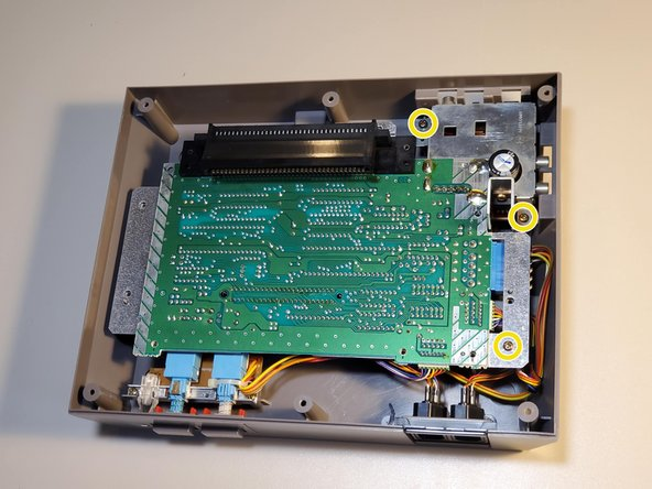 Remove three 13.25mm Phillips screws to free the motherboard from the bottom housing.