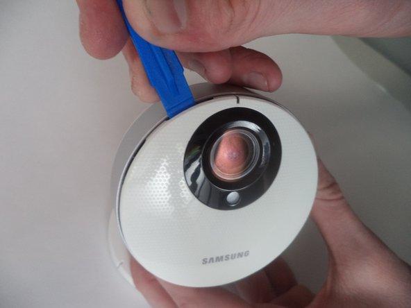 Localisez une petite ouverture autour du panneau avant de la caméra.