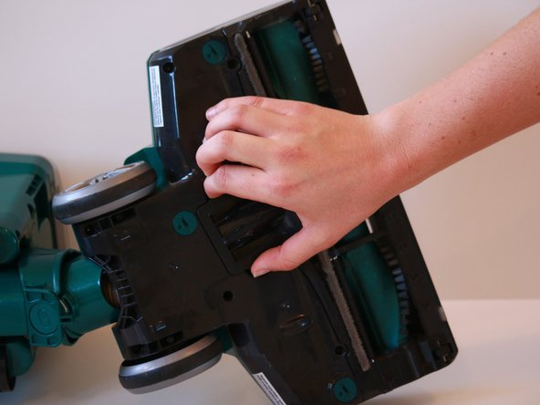 Squeeze the sides of the roller brush cover release clasp, and swing the cover open.