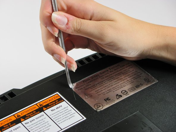 Peel back both the silver sticker and the white barcode sticker to reveal two additional screws.