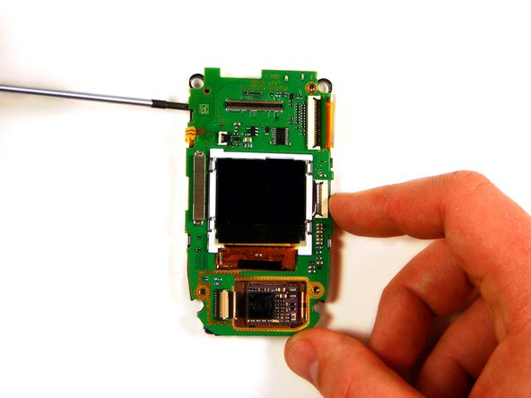 Using the head of the flathead screwdriver, pry the silver plastic casing of the LCD from the video logic board.