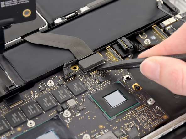 Use the flat end of a spudger to pry the SSD cable connector up off its socket on the logic board.