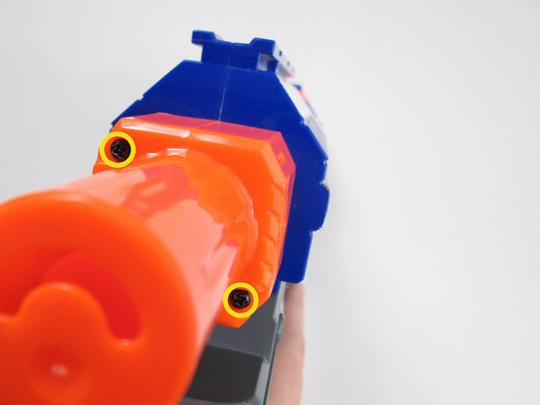 Looking from the rear of the rifle, remove the two 10 mm phillips screws holding the orange cap to the butt of the rifle.