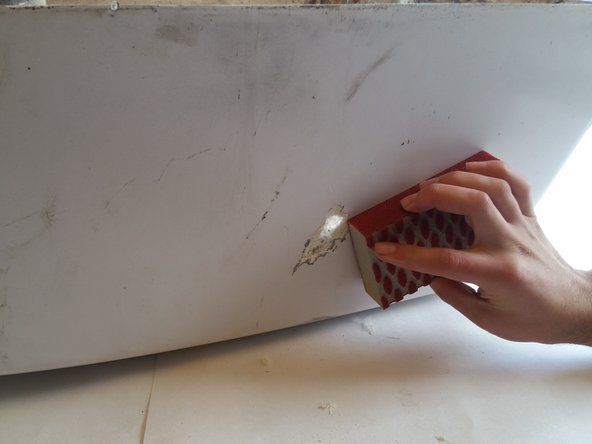 Begin by sanding both sides of the hole surface with the rough sandpaper until the larger pieces of old fiberglass are smooth.