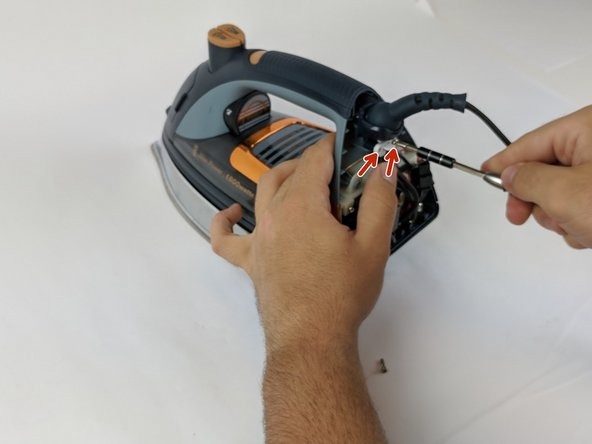 Use the Philips head #0 screwdriver to remove the two 11.77mm screws holding the white clamp to the iron.