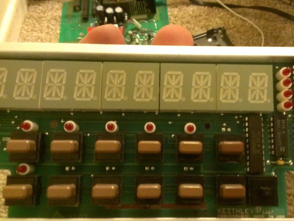 The display is comprised of some multidigit LEDs, some buttons and a few IC's to drive the leds and buttons. The button with no cap is to activate the calibration function