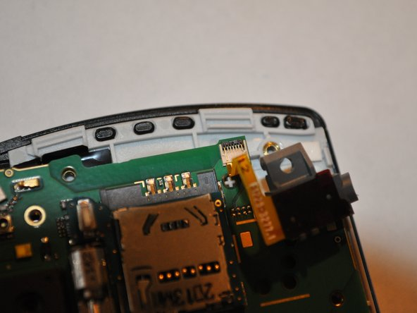 Remove the headphone jack by carefully moving the dark plastic clip on the connector to 90 degrees