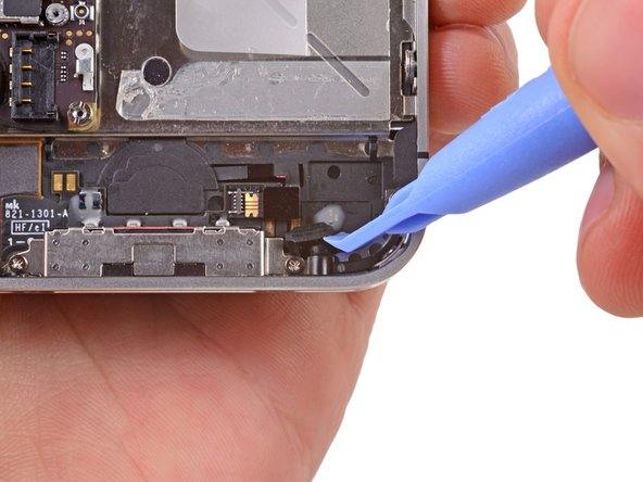Carefully pull the rubber microphone holder out of its tube in the bottom edge of the iPhone.