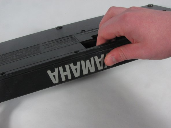 Place your fingers in the battery compartment, and place your thumb on the back of the keyboard.
