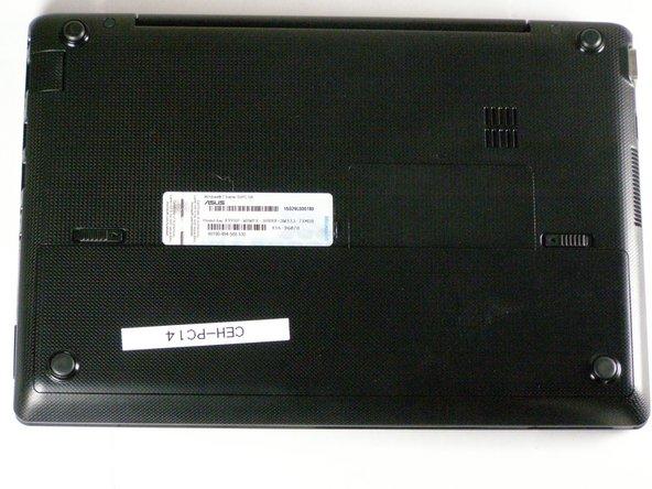 Posez l'ordinateur portable à plat sur une surface dure avec le dessous orienté vers le haut et la batterie sur le côté le plus proche de vous.