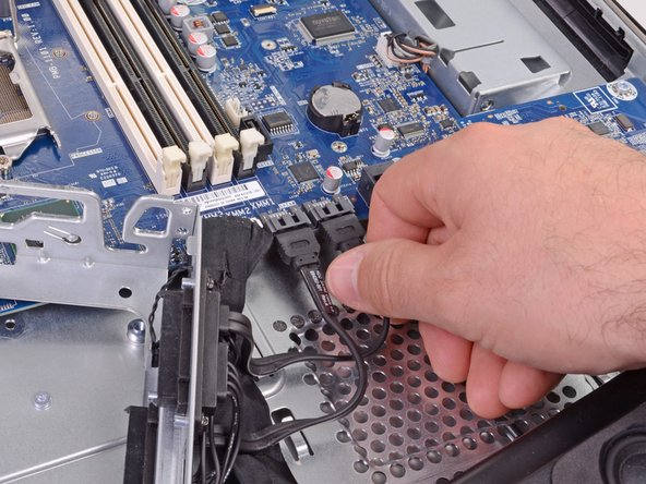 We're getting down to some serious deconstruction now. A few SATA connectors come out and the hard drive bracket is free.
