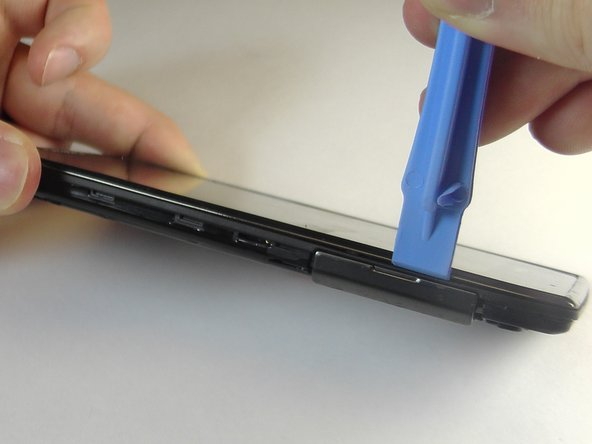 Insert the plastic opening tool between the rear case and motherboard assembly.