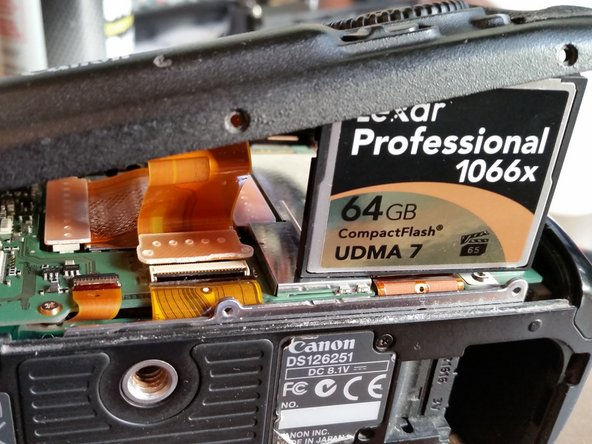 To remove the connecting flex cable, something can be used to hold it up (CF card was used in the example photo), or simply hold it up with another hand