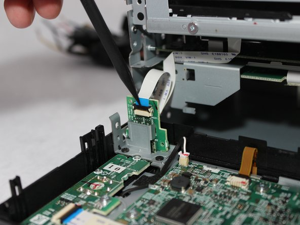 Flip up the black clasp with the spudger to disconnect the small white ribbon cable from the vertical board.
