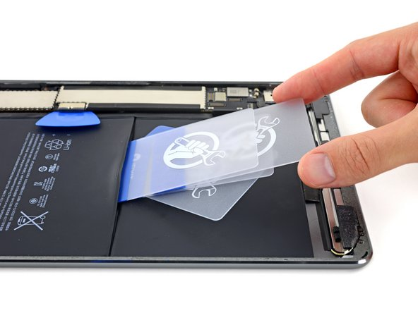 Insert multiple additional cards between the first and second card to create a wedge that will begin to lever the battery away from the rear case.