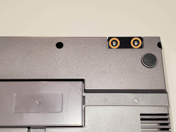 Remove two 7.25mm Phillips screws from the bottom of the system. Lift the controller port faceplate up and away.