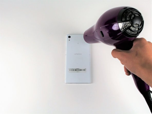 Use a hair dryer to heat each corner of the phone.