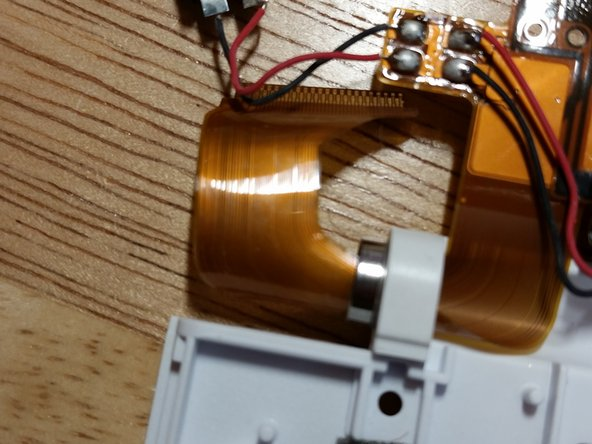 If the flex cable is damaged, then you're out about $8 as of this writing. Exercise extreme caution with this fragile piece, carefully rolling it into a tight cylinder. If the flex cable is damaged, there is no way to repair the LCD, and the entire module must be scrapped. Remove and set aside the metal piece.