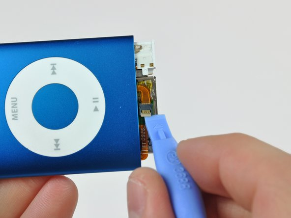 Use the edge of an iPod opening tool to flip the ZIF cable lock up toward the headphone jack.