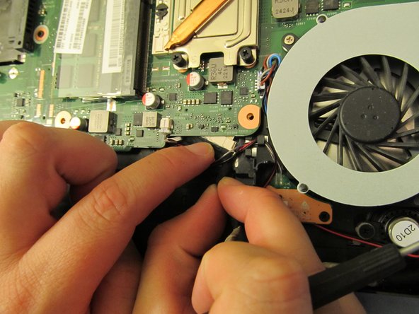 Carefully tug the LCD cable out from under the motherboard.