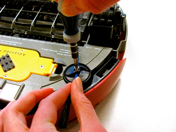 Using the Phillips #1 Screwdriver, unscrew the 7.2 mm Phillips #1 screw while holding the edge brush in place.