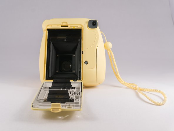 Press the tab down in order to unlatch the film compartment cover.