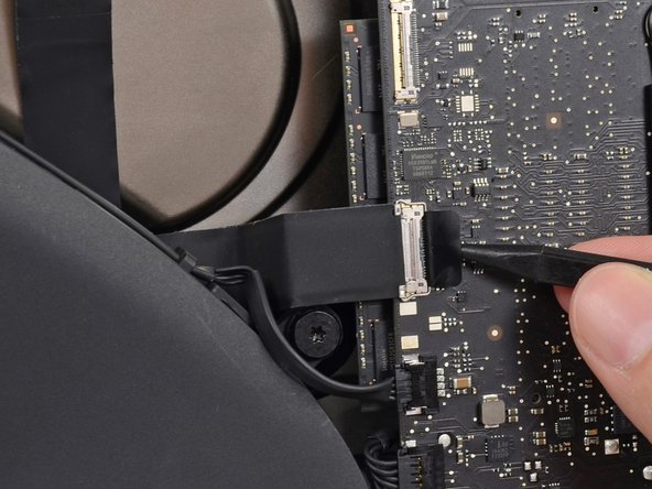 Use the tip of a spudger to flip up the metal retaining bracket on the iSight camera cable located on the logic board.