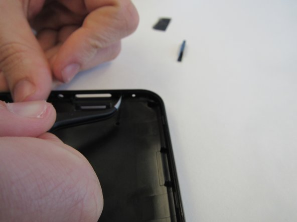Dislodge the volume button from the upper right corner of the tablet's back cover using the tweezers