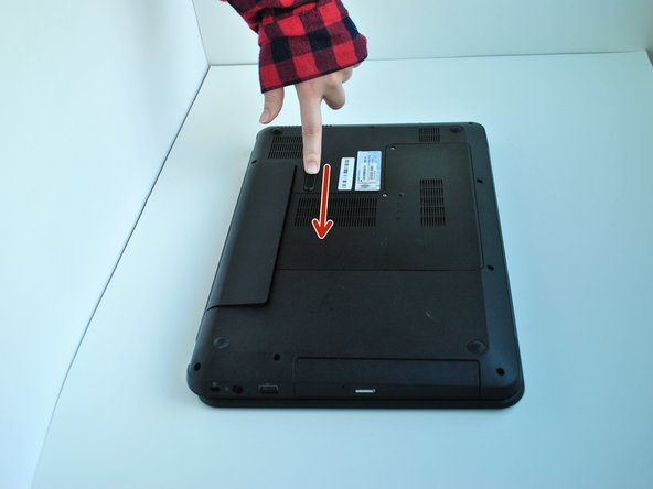 Slide the switch under the battery compartment to release the battery.