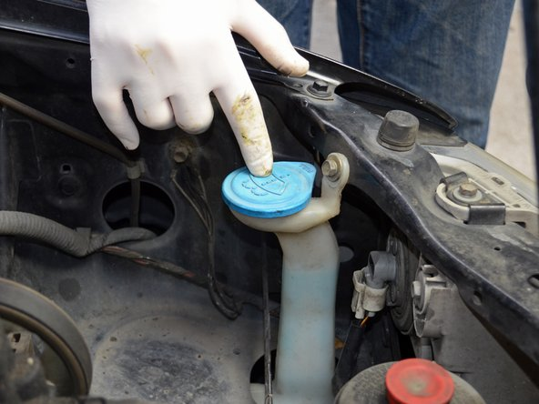 Locate the window washer fluid reservoir in the front right corner of the engine bay.