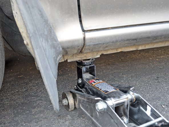 Begin by placing a jack under the lifting point. It is on the driver's side of the car, below the rocker panel and just behind the front wheel.
