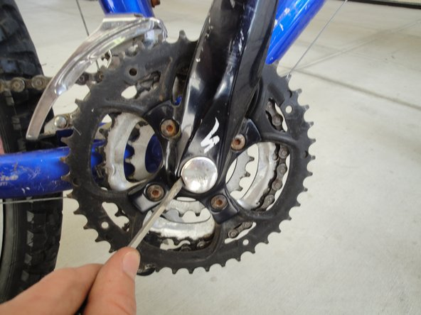 Take cap off the crank arm with flat head screw driver. It should just pop off.