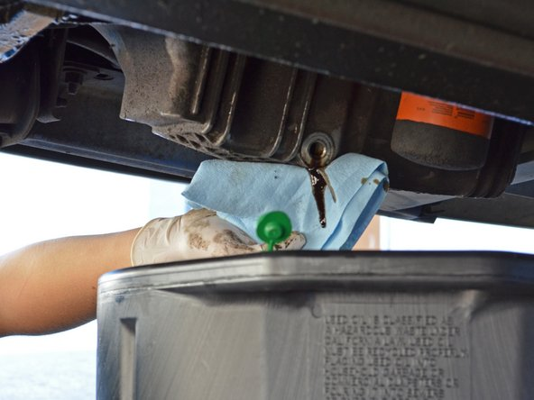 Once the old oil has slowed to a drip, use a rag or towel to clean the excess oil from the drain hole.