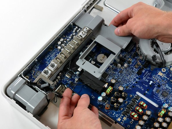 Gently lift the logic board from its left side to clear the two pins mounted to the midplane.