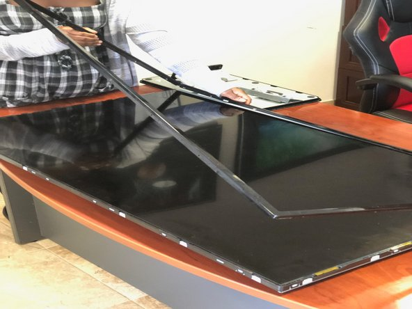 Next, we lift up the frame from in front of the TV (those tiny side screws did the work) and set it aside.
