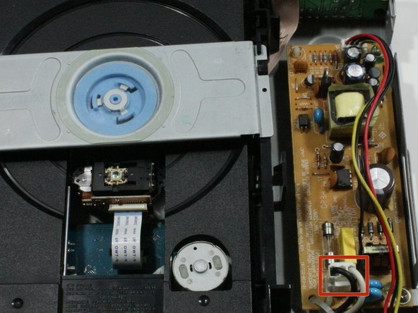 Orient the device to locate the power supply board on the far right corner. Use needle nose pliers to  pull the white connector from the power supply board.