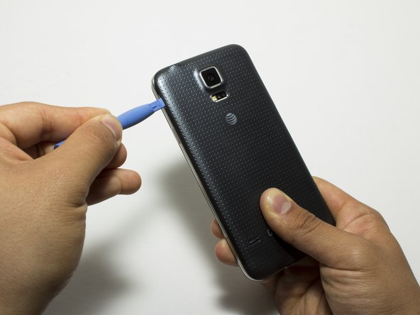 Remove the rear case by using moderate force to pry the divot on the left of the rear facing camera with a plastic opening tool or your fingernail.