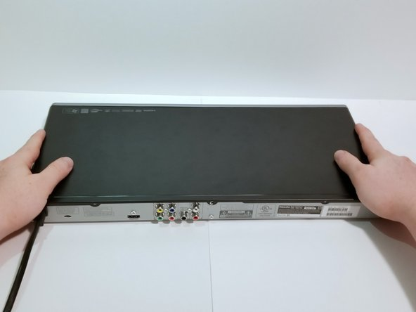 Remove the top plate of the DVD by firmly grasping the player on both sides.
