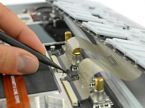 Unlock the flex cables by pushing the two black nibs on both sides of each connector.