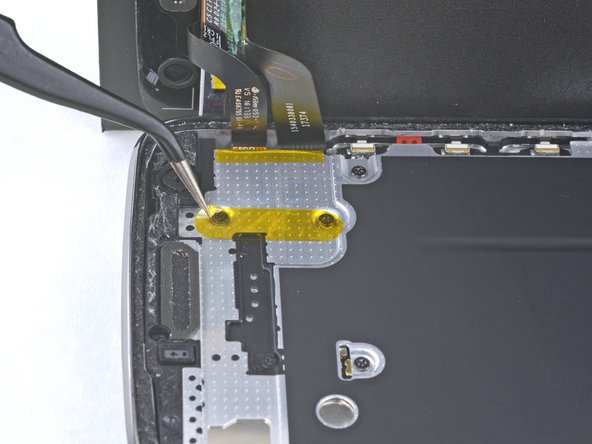 Remove the yellow sticker covering two of the black Phillips screws below the earpiece.