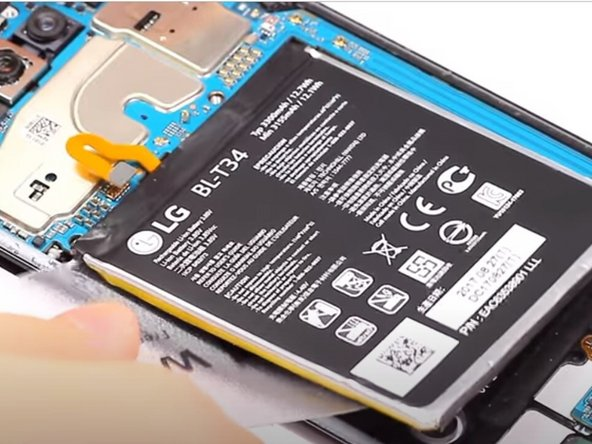 Use the plastic card to pry the battery upwards from its slot.