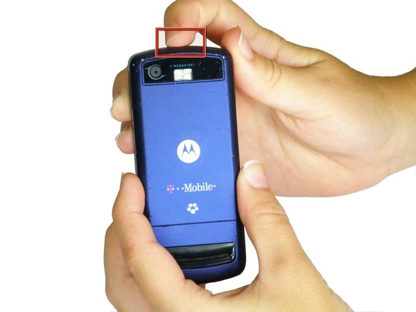 Press the panel release button on the top of the phone and simultaneously pull the rear panel away from the phone.
