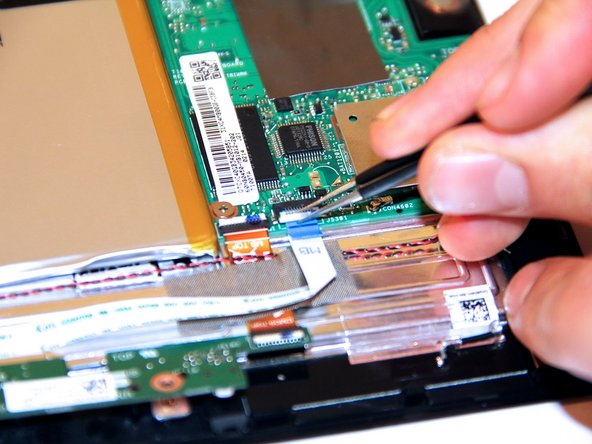 Lift up the power button cable retention clip on the motherboard and pull the cable out.