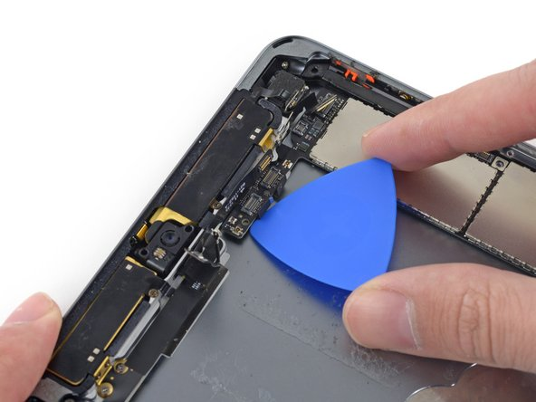 Carefully slide a second opening pick under the logic board to the right of the front-facing camera.
